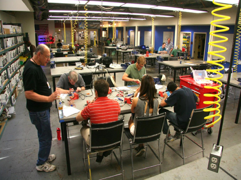 Makerspace: Large workshop with people working together at tables creating 3D objects.
