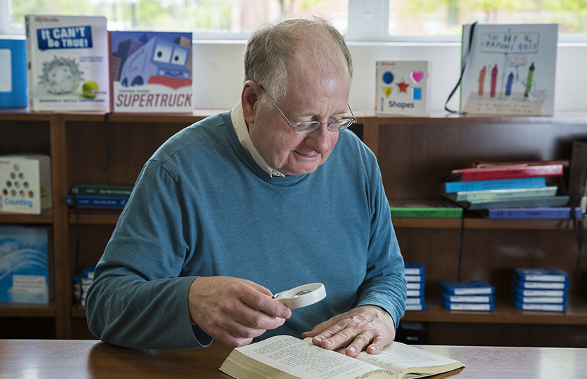 Elderly man using magnifying glass to read in library.