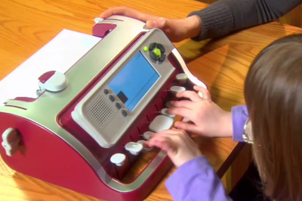 A young girl who is visually impaired practices her brailling skills on a Perkins SMART Brailler.