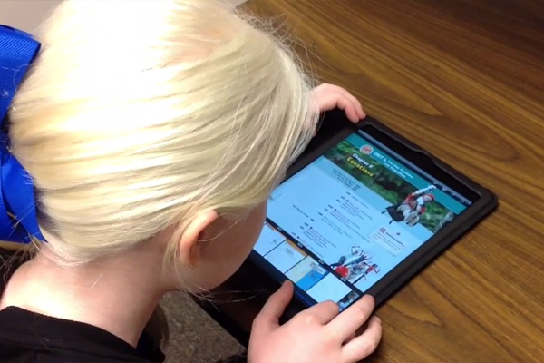 A young girl with Albinism as she accesses her math textbook on an iPad.
