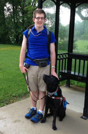 boy with glasses in blue shirt wearing a backpack standing next to black guide dog