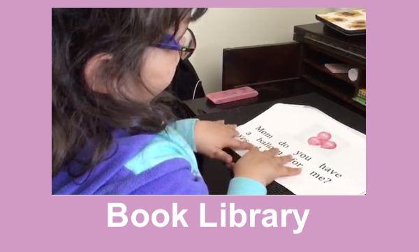 Young girl with reading a teacher-created print/braille book with her hands on the braille.