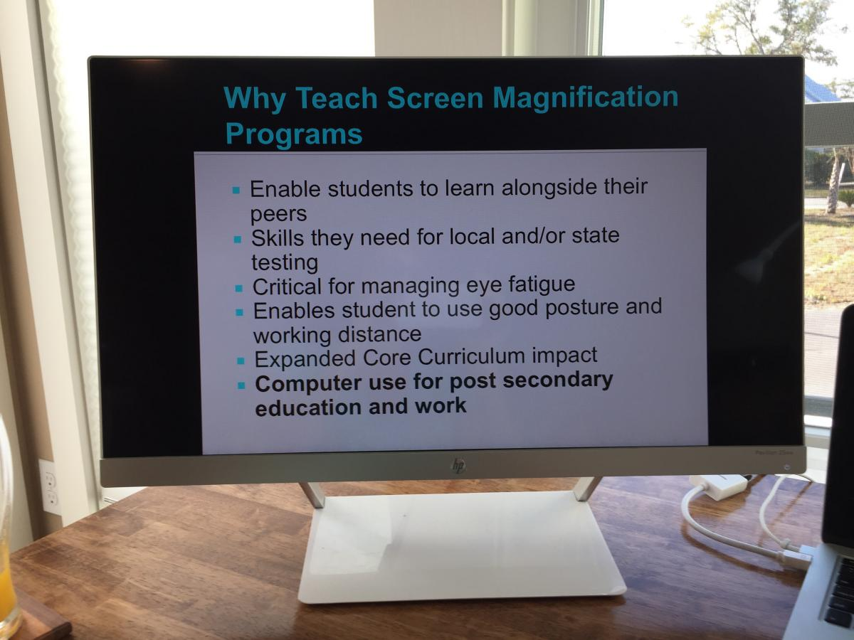 "Photo of a computer displaying a PowerPoint slide entitled, ""Why Teach Screen Magnification Programs"""