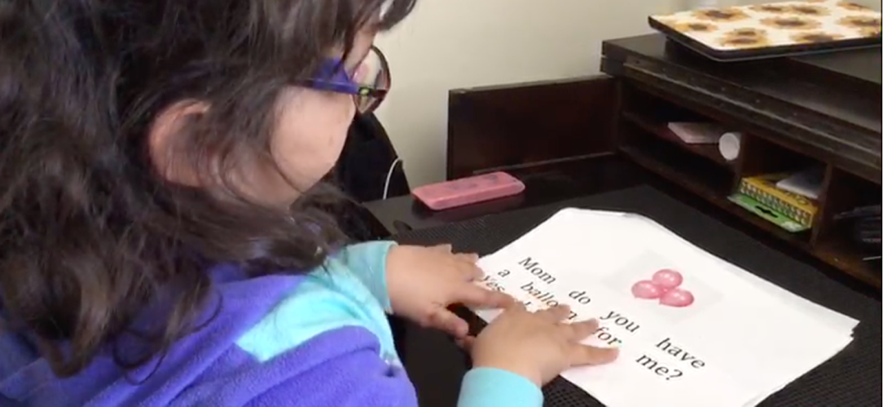 Young multimodal emerging reader reading a teacher-created large print and braille book with her fingers on the braille.