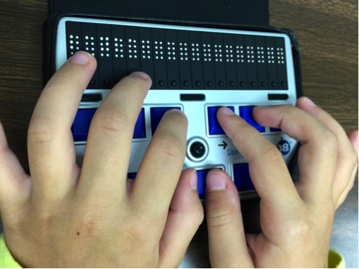 Young fingers aligning with corresponding braille input keys to create a braille chord command.
