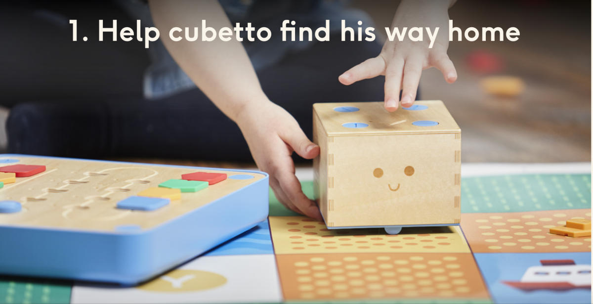 "1.Preschooler placing Cubetto on the map with the board beside him.  Text: ""Help Cubetto find his way home."""