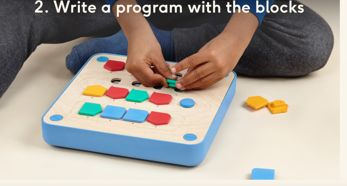 "Preschooler placing coding pieces in board; Text: ""2. Write a program with the blocks."""