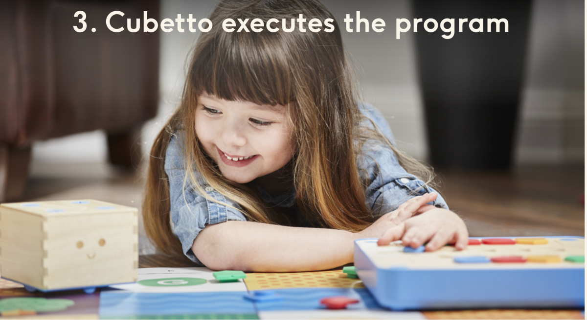 "Smiling preschooler pressing the Go button and watching Cubetto move on the map; ""3. Cubetto executes the program."""