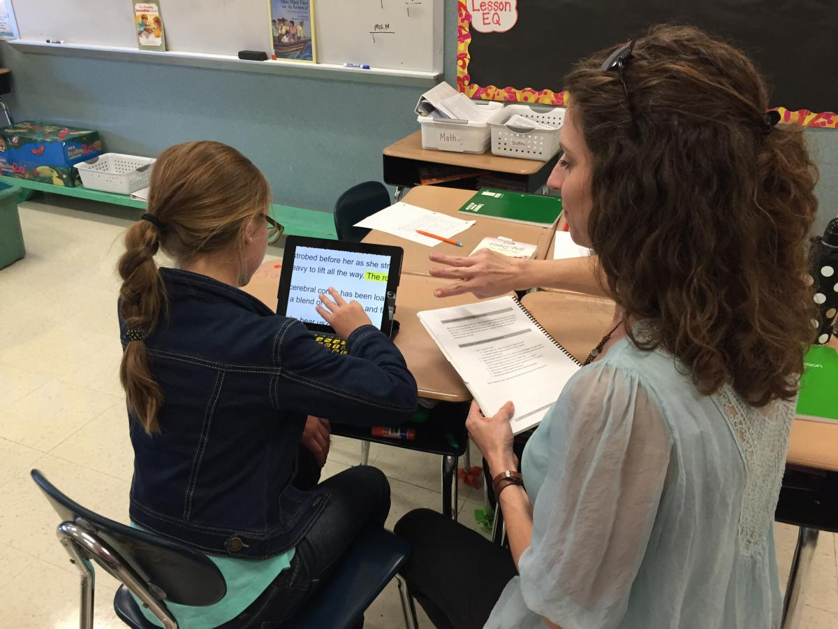 Teacher holding a manual with 3-fingers extended standing beside a student who is learning to use a 3-finger swipe on an iPad