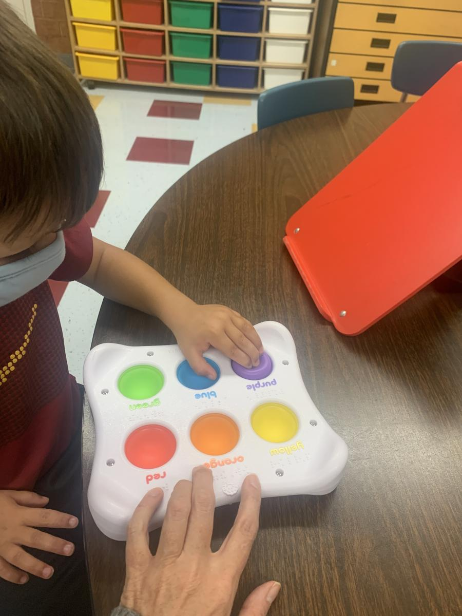 photo of 3 year old visually impaired boy wearing a face mask using multiple fingers to push the purple Dimpl Duosilicone button.