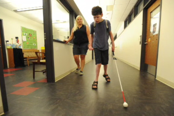 A photograph of an adolescent boy who is blind, using a cane while navigating a school hallway.