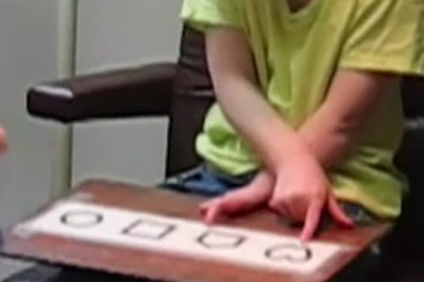 A young girl who is visually impaired and multiply disabled undergoing a LEA symbol matching test to measure her visual acuity.
