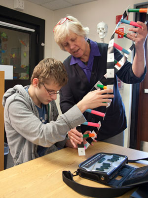 Student examining a tactile model of DNA with his teacher