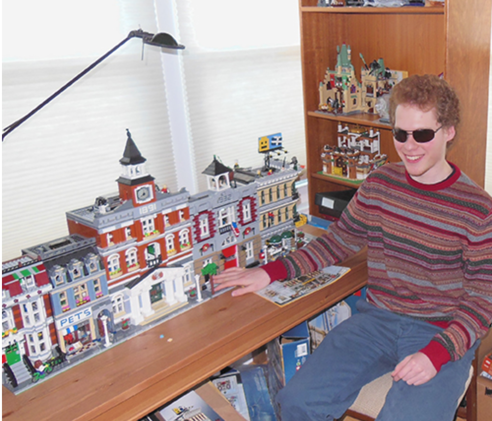 Matthew sitting  in his room, with numerous large LEGO buildings and completed kits covering his desk and bookshelves.