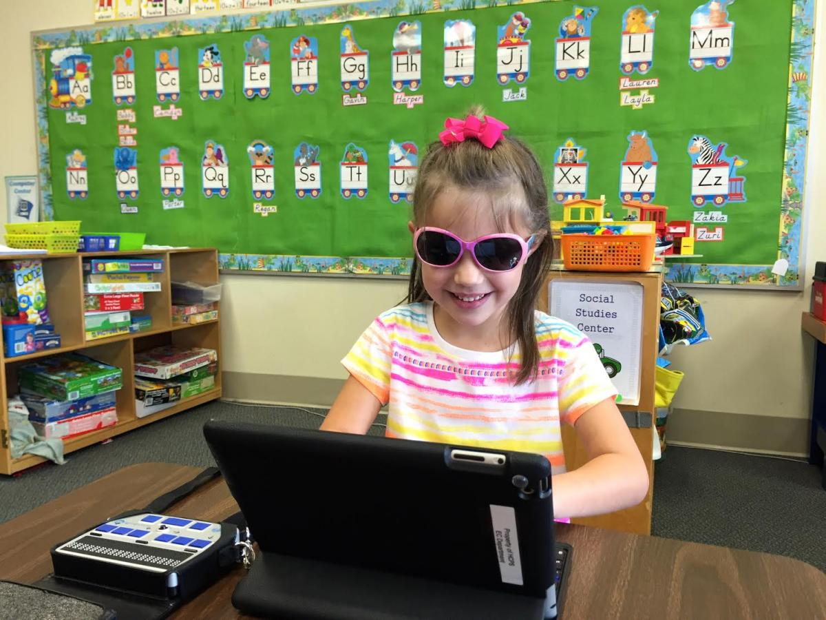 Smiling 4 year old using an iPad and Bluetooth keyboard with a braille display beside her on a classroom desk.
