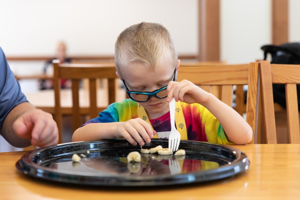 A young boy with glasses uses fork and fingers at snack time