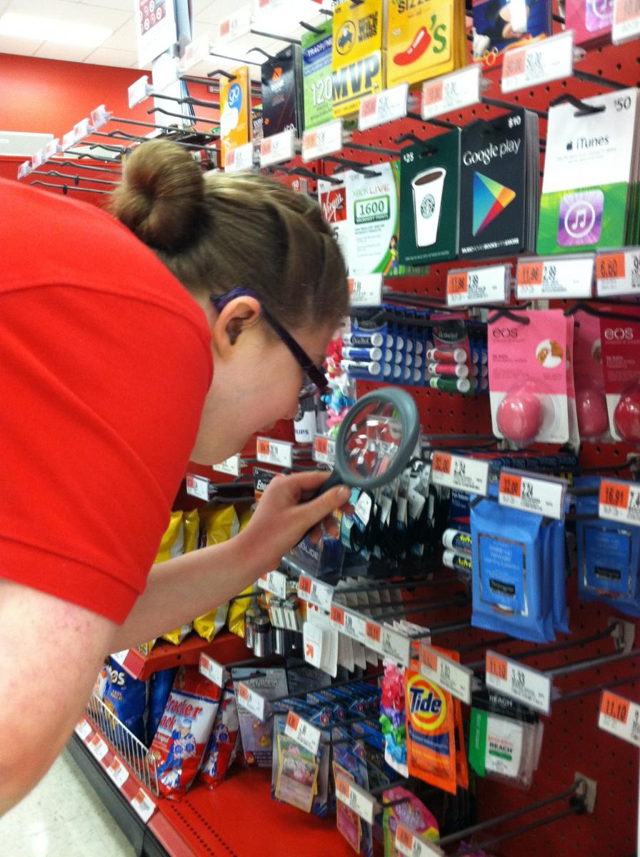Student using a magnifying glass in a store