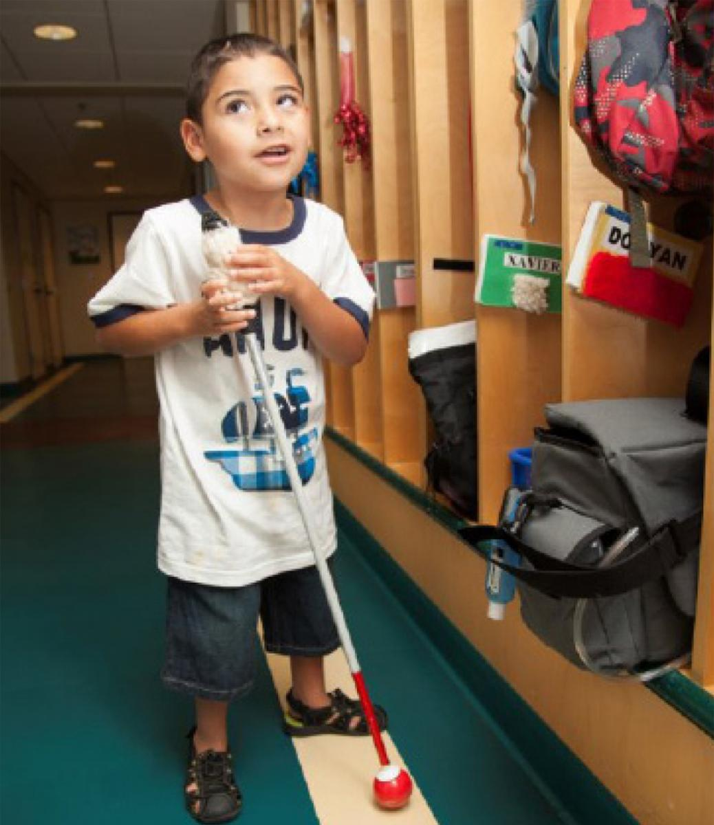 A young boy navigating the hall with his cane.
