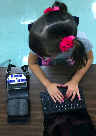 Layla sitting at her desk with her hands on her iPad's Bluetooth keyboard and the braille display to her right.