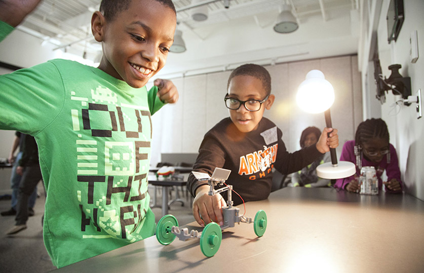 Two young boys working on a small robot.