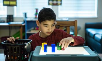 A student using colored shapes on a lit tabletop.