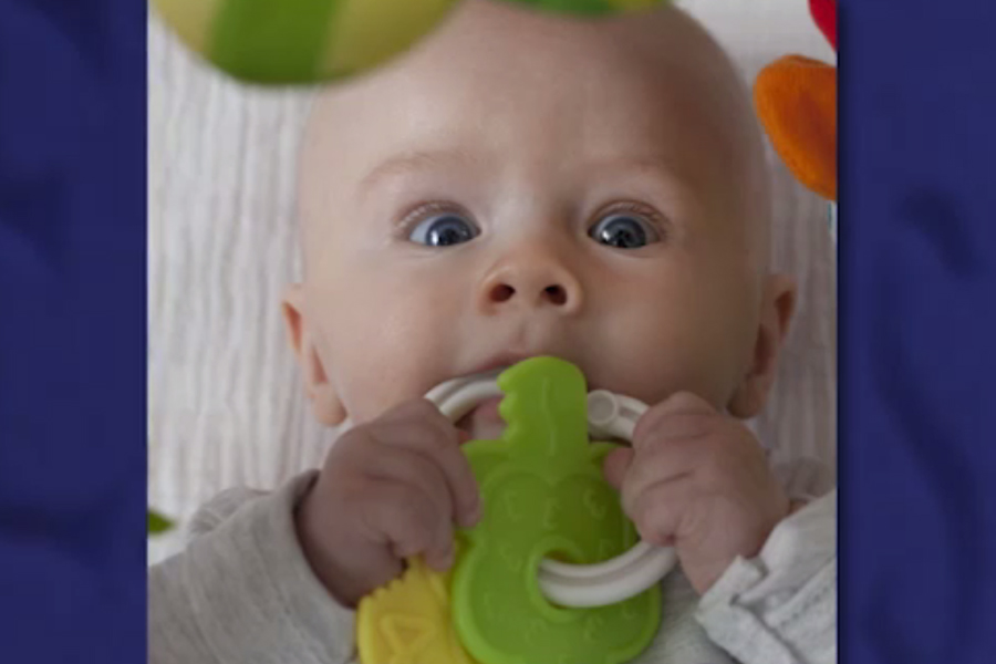 Photo of an infant with a plastic ring of colorful, key-shaped objects attached.