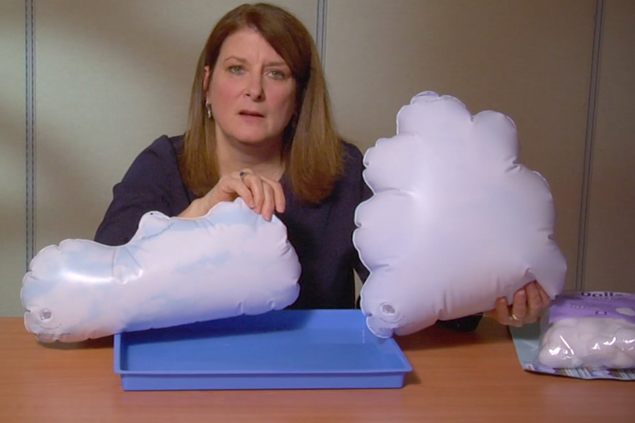 Selma holds up two small, white, inflatable clouds in low horizontal and vertical shapes.