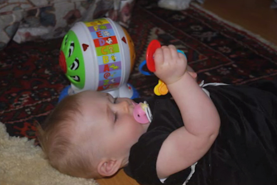 Photo of an  infant girl who is visually impaired, on her back, grasping a toy in her hands.