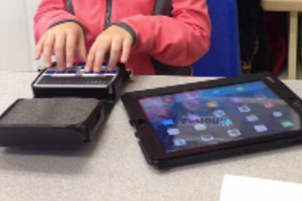 A 4-year-old girl who is blind She is working with her iPad and refreshable braille display.