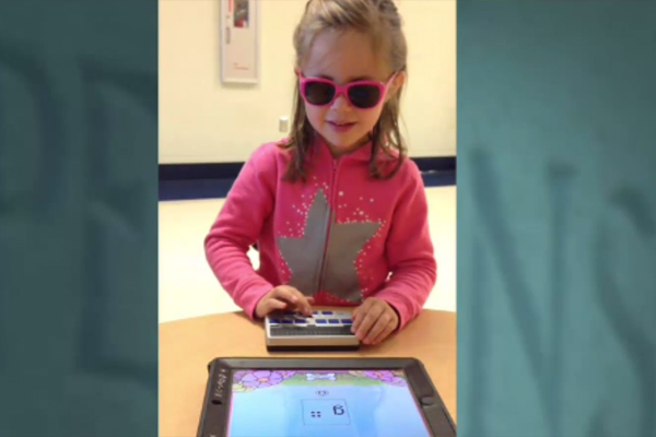 A 4-year-old girl who is blind learning braille by using an iPad app called Exploring Braille with Madeline and Ruff.