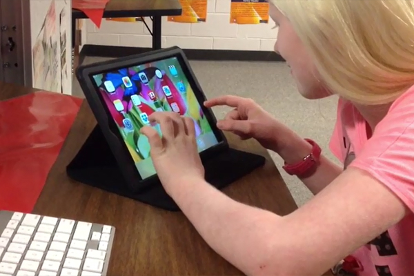 An adolescent girl with Albinism is shown using the voice over accessibility tool on an iPad.