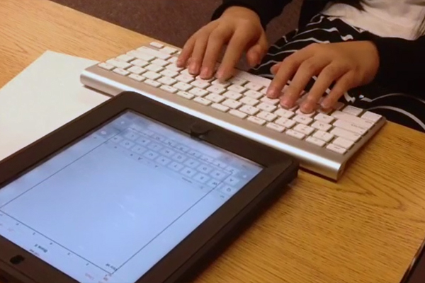A young blind girl works with her TVI to type and print a document for her teacher.