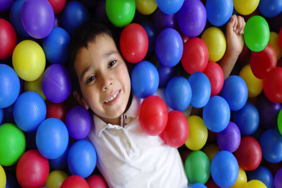 Picture of a little boy in a ball pit, getting bombarded with all sorts of tactile information to his entire body.