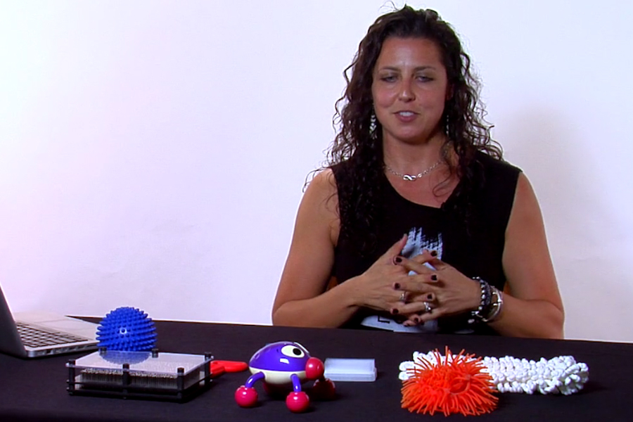Amanda sits in front of different examples of fidget toys that have all sorts of size and shape.