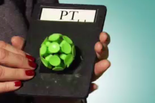 Sharon holds a black card with a white label that reads PT. The symbol for PT is a small, green and white suction ball.