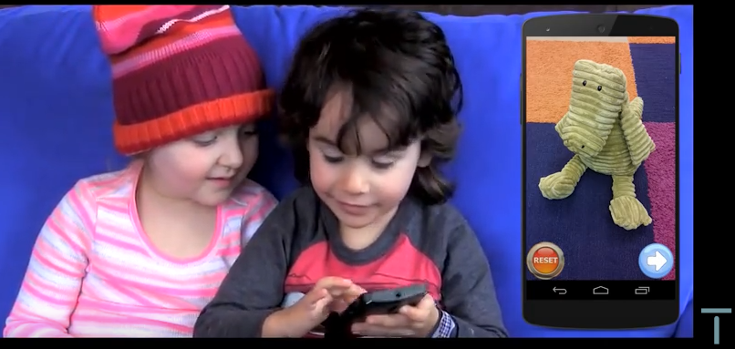 Two preschoolers playing with the Tanvas app: app screen displaying a textured picture of a stuffed corduroy dinosaur.
