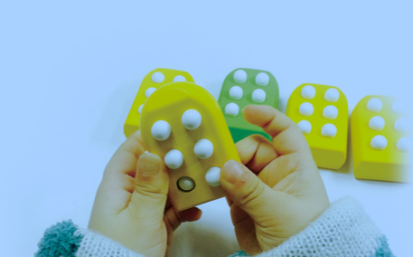 Preschooler hands pushing in pins on a Taptilo block to create a braille letter.