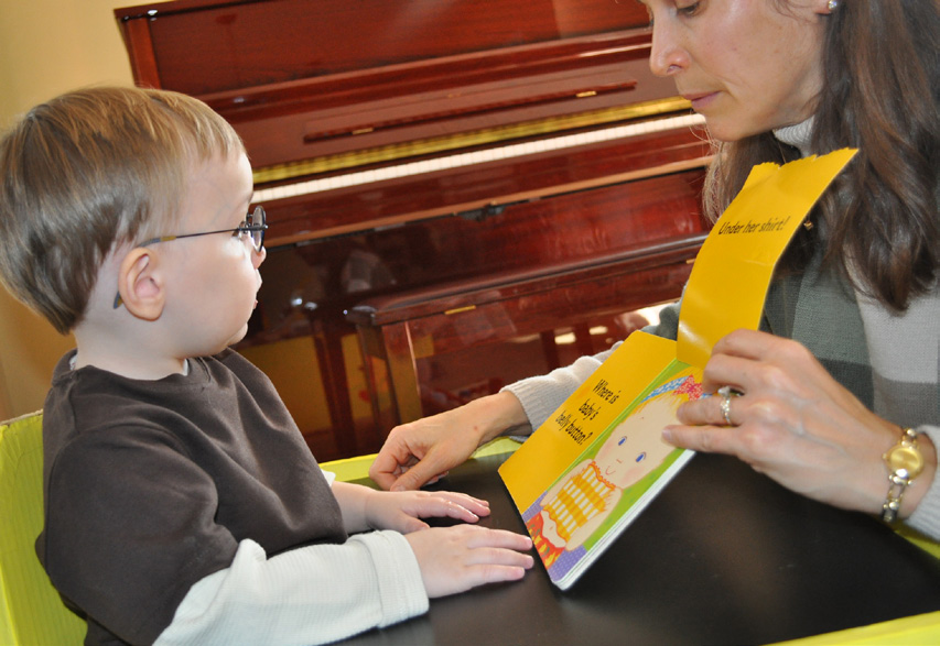Young boy with glasses looks at picture book with teacher
