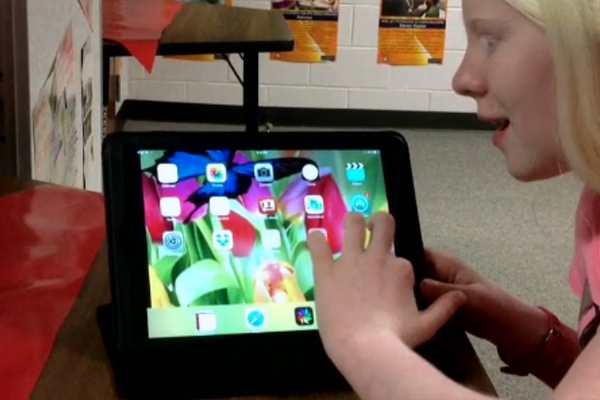 A young girl with Albinism is learning to use the Voice Over feature of her new iPad.