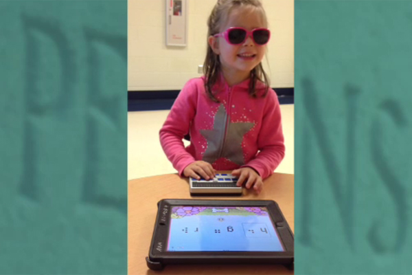 Using an iPad that has been linked to her refreshable braille display, a young girl uses the app Exploring Braille with Madeline and Ruff.