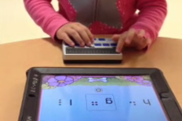 A young girl who is blind using her refreshable brailler that has been paired with an iPad.