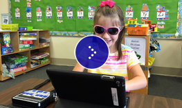 Layla is sitting at her desk and typing on her iPad.
