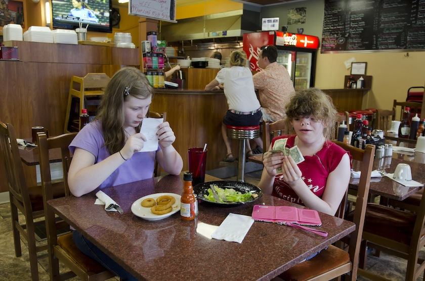 Two girls examine their bill in a restaurant.