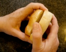 two hands holding a bagel cut in half