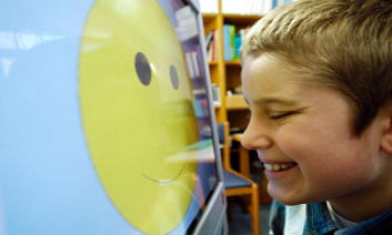Boy looking at screen with smiley face