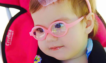 Girl with pink glasses in a stroller