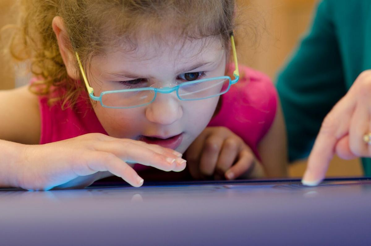 Girl with glasses uses iPad