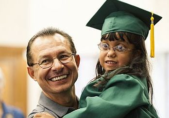 young girl wearing graduation cap and gown