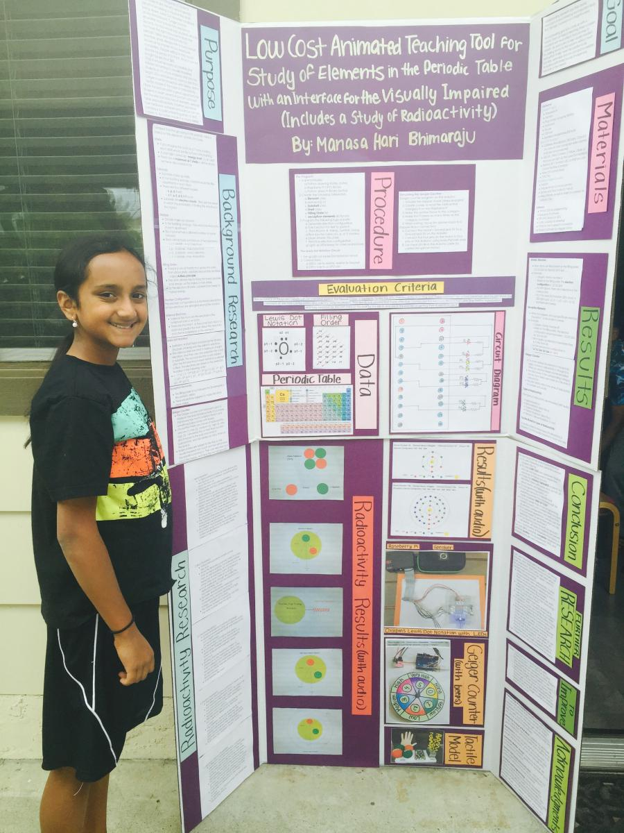 Hari in front of science fair project