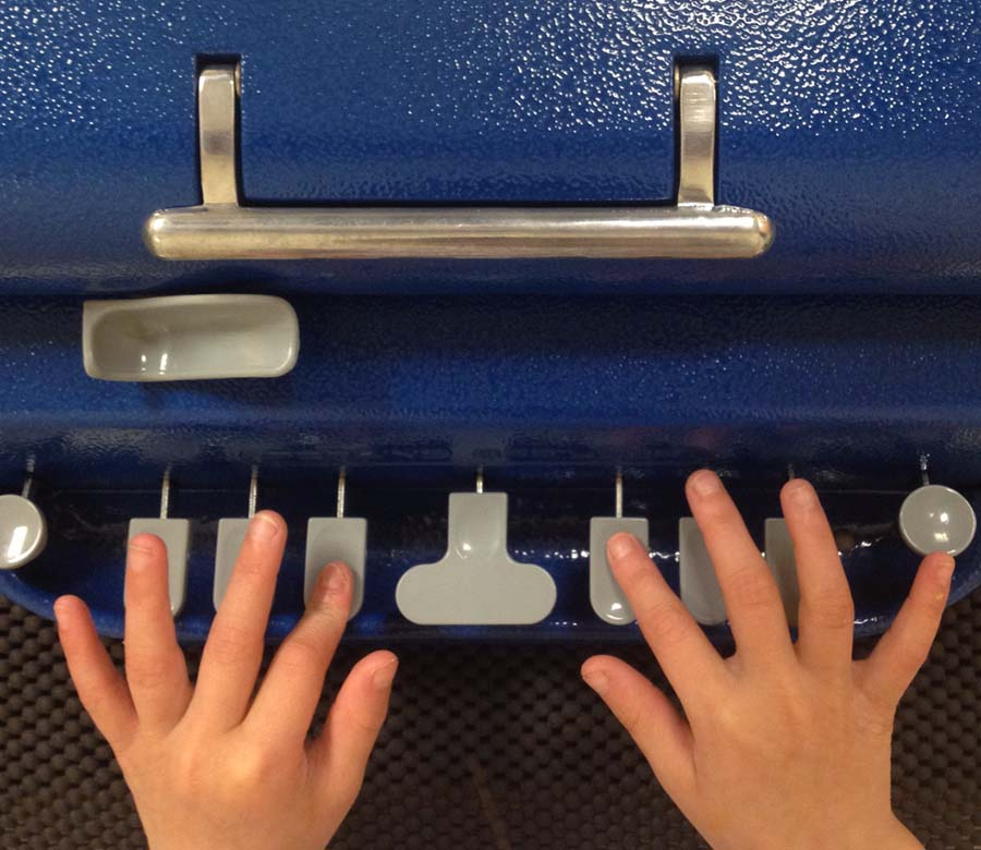 Child's hands on keys of braillewriter